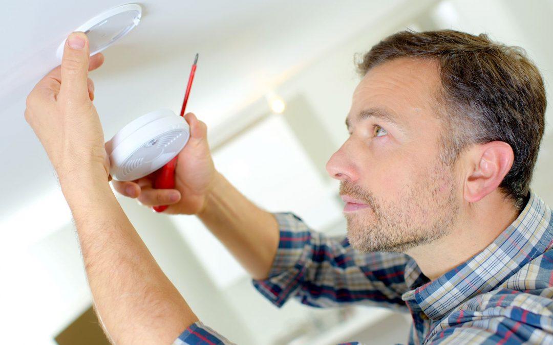 handyman changing smoke detector batteries in Colorado home